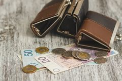 Polish zloty with little wallets on the old wooden background royalty free stock photography