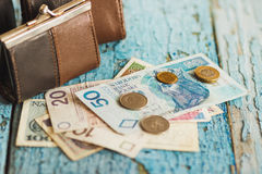 Polish zloty with little wallets on the old wooden background Stock Photo