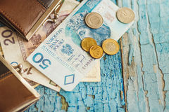 Polish zloty with little wallets on the old wooden background Stock Images