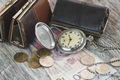Polish zloty with little wallets and pocket clock on the wooden background Stock Photos
