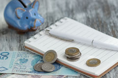 Polish zloty, notebook and piggy bank on the wooden background Royalty Free Stock Image