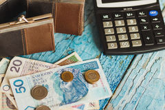 Polish zloty with a wallet and calculator, wooden background Stock Photography