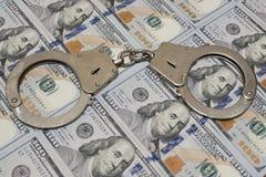Polishandbojor mot hundra dollarräkningar USA Begreppskränkning av lagen, korruption, finansiellt bedrägeri royaltyfri bild