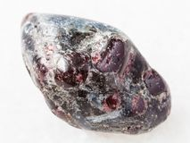 Polished Almandine garnet crystals on white marble. Macro shooting of natural mineral rock specimen - polished Almandine garnet and biotite crystals in gemstone royalty free stock photo