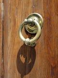 Polished Brass Door Knocker, Rome, Italy. A polished brass door knocker on a wooden door showing grain, Rome, Lazio, Italy Stock Photography
