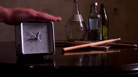 On a polished brown wooden table, with a reflection, there are square silver with a white dial, a clock and drum sticks. With legs, with a note book. The hour stock footage