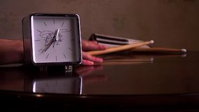 On a polished brown wooden table, with a reflection, there are square silver with a white dial, a clock and drum sticks. With legs, with a note book. The hour stock video footage