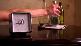 On a polished brown wooden table, with a reflection, there are square silver with a white dial, a clock and a note book. With legs. The hour hands show 12:45 stock footage