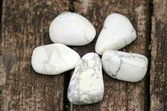 Polished howlite minerals set. Set of five howlite gemstones on a wooden background Royalty Free Stock Image