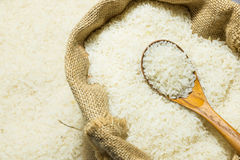 Polished jasmine rice and wooden spoon in gunny sack Royalty Free Stock Photos
