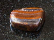 Polished Jaspillite stone on black royalty free stock photos