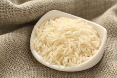 Polished long rice grains in white ceramic bowl Stock Photography