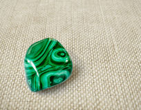 Polished malachite stone on canvas background Royalty Free Stock Photo