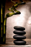 Polished Massage Stones Cairn and Bamboo in Spa. Polished smooth black hot massage stones stack in a Zen inspiration cairn with bamboo plants on an old weathered stock photography