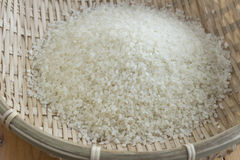 Polished rice in a bamboo basket Stock Images