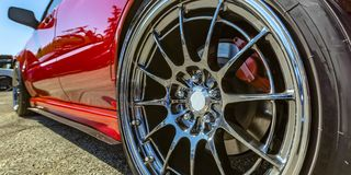 Polished rim of a bright red car. Left back wheel of a bright red car with polished rim. A reflection of another car can be seen on the car and rim`s glassy stock photo