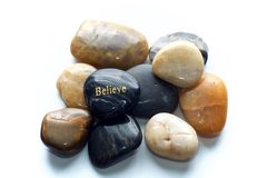 Polished stones with believe rock. A gray polished river stone with the word believe in gold on a pile of many polished rocks. Over white, not isolated stock photo