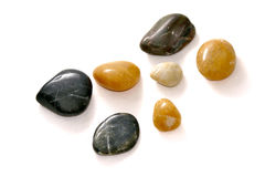Polished stones on white. Collection of smooth polished stones on white with shadows royalty free stock photography