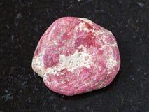 Polished Thulite gemstone on dark background Royalty Free Stock Image