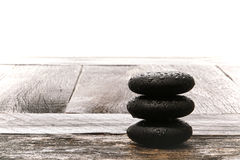Polished Wet Massage Stones Cairn on Vintage Wood. Wet polished smooth hot massage black stones with water drops and droplets in a Zen style cairn on a vintage royalty free stock images