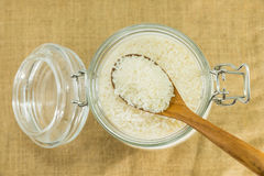 Polished white rice in glass jar on gunny sack texture Stock Photo