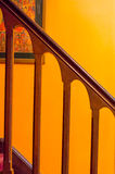 Polished wooden railing orange wall Stock Image