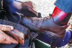 Polishing brown leather shoes with polishing grease royalty free stock image
