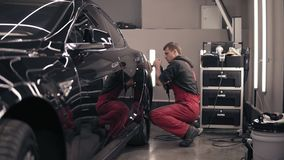 Polishing car with polish mashine. Worker in red suit cleaning a black expensive car. stock video