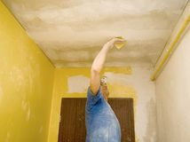 Polishing ceiling. A man working. Renovating works, polishing the ceiling with sandpaper Royalty Free Stock Photos