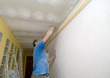Polishing ceiling. A man working. Renovating works, polishing the ceiling with sandpaper Stock Images