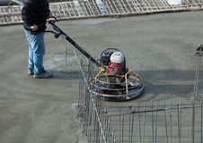 Polishing concrete. Construction worker produces the grout and finish wet concrete with a special tool. Float blades. For smoothing and polishing concrete stock images