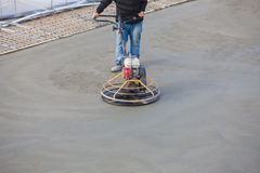 Polishing concrete. Construction worker produces the grout and finish wet concrete with a special tool. Float blades. For smoothing and polishing concrete stock image