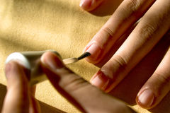 Polishing Fingernails. A woman applies a clear coat of fingernail polish to her fingernails Royalty Free Stock Photography