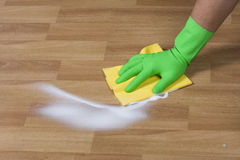 Polishing floor. Cleaner is cleaning wooden parquet floor royalty free stock photo