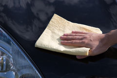 Polishing the hood of a car with a chamois Royalty Free Stock Images