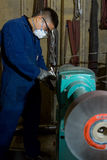 Polishing metal in workshop Royalty Free Stock Photo