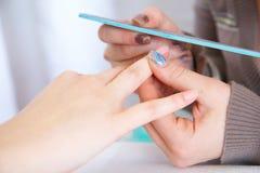 Polishing  a nail Stock Images