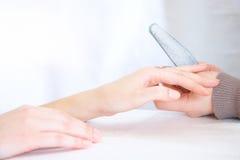 Polishing a nail. Polishing of a surface of a nail royalty free stock image