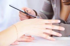 Polishing a nail. Polishing of a surface of a nail stock photo