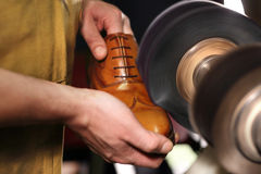 Polishing shoes. Polisher cobbler polishes on brown shoes Stock Photography