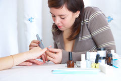 Polishing of a surface of a nail. Girl polishing of a surface of a nail stock photo