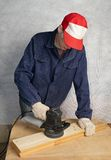 Polishing the wood. The worker polishes wooden board Royalty Free Stock Photos