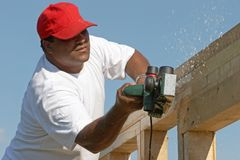 Polishing wood frame. Worker man polishing wood frame on anew construction royalty free stock image