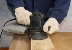 Polishing wooden board. The worker polishes wooden board Stock Photos