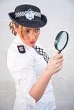 Poliskvinna 69 med förstoringsglaset Fotografering för Bildbyråer