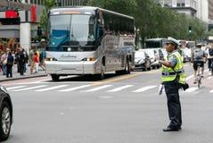Poliskvinnan riktar trafik Arkivfoto