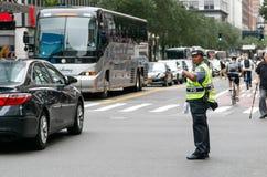 Poliskvinnan riktar trafik Arkivbilder
