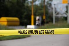 Polislinjen gör inget kors med bensinstationbakgrund i brottsce Royaltyfri Bild