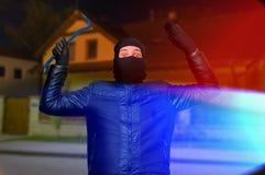 Polisljus och den maskerade inbrottstjuven eller tjuven med balaclavaen är arre arkivfoton