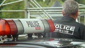 Polisman i laddningen som säkrar händelsen, säkerhetsvakt, arbetsuppgift stock video